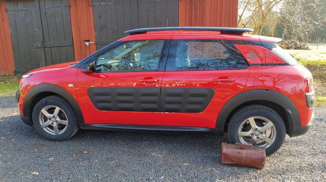 Tjänstebilen är en röd Citroën C4 Cactus. Bredvid bilen står veterinärväskan packad och klar för nya sjukbesök.