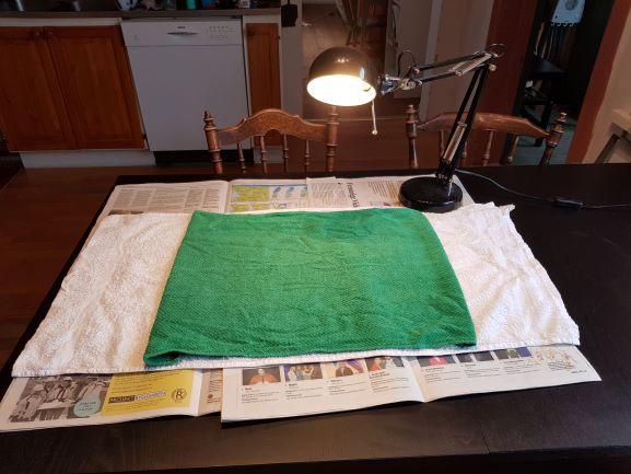 En förberedd operationsplats för kastration av katt. Några tidningar på ett köksbord, en ren grön handduk ovanpå och en skrivbordslampa för extra belysning.