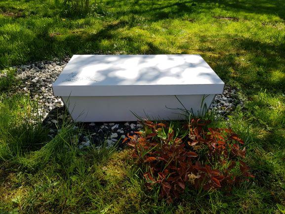 En vit kista i wellpapp mot en bakgrund av grönt gräs, växter och svarta och vita stenar. Under oktober månad bjuder vi på kistan vid hembegravning av djur.